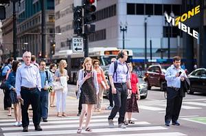 people crossing street holding mobile phones