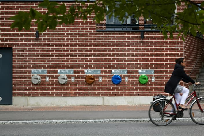 Woman cycling past the recycling bins in Kalasatama