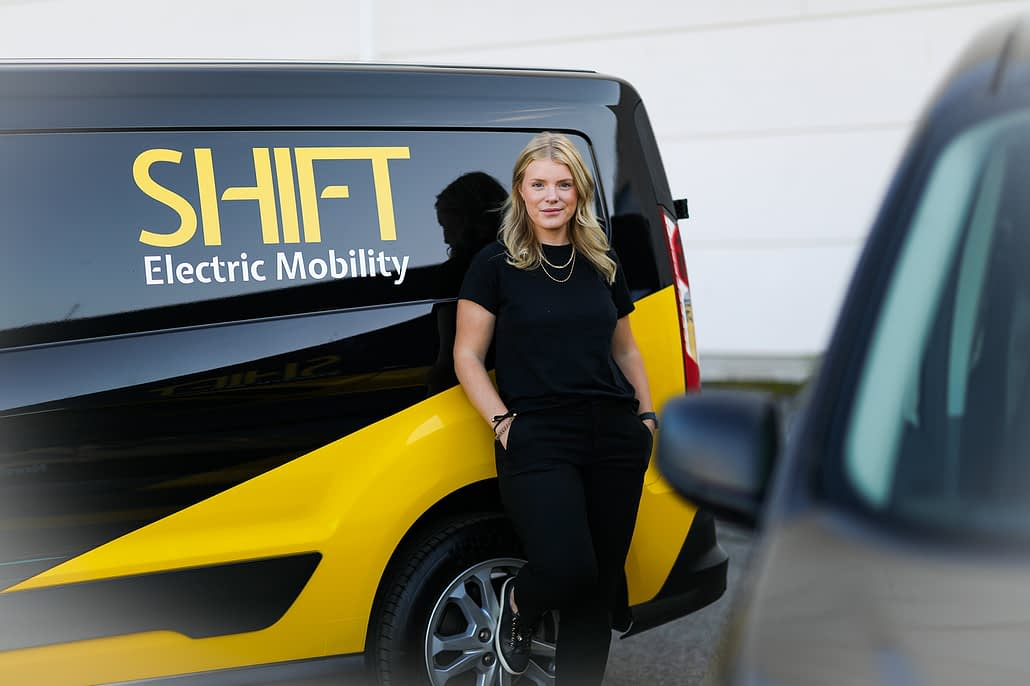 Woman in front of SHIFT Electric Mobility vehicle.