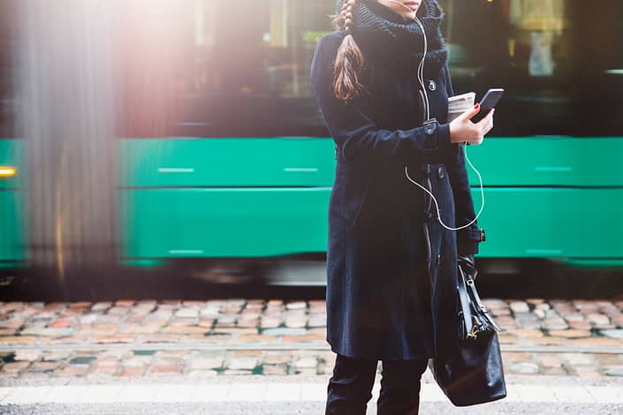 Girl holding mobile phone tram in the background